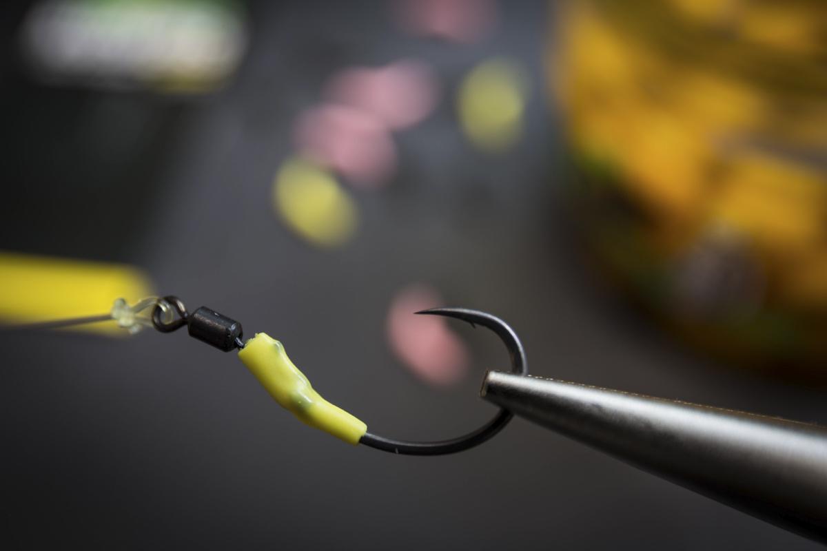 Ein kleines Stückchen Schrumpfschlauch wird über den Haken geschoben und anschließend über heißem Dampf geschrumpft. Alternativ dazu, kann auch ein fertig geformter Kicker verwendet werden.